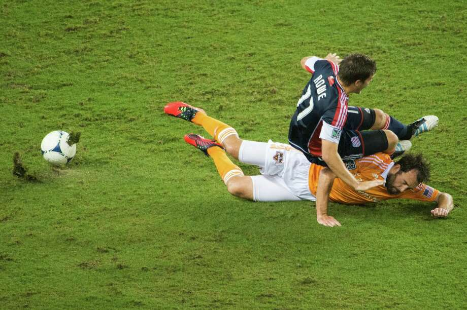 New England Revolution midfielder Kelyn Rowe (11) crashes down onto Houston Dynamo midfielder Adam Moffat (16) during the first half on Saturday, Sept. 29, 2012, at BBVA Compass Stadium in Houston. Photo: Smiley N. Pool, Houston Chronicle / © 2012  Houston Chronicle