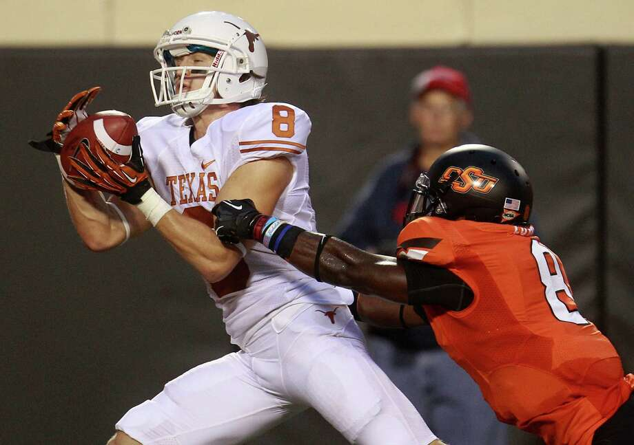 Texas' Jaxon Shipley hauls in a touchdown reception in front of Oklahoma State safety Daytawion Lowe for one of his two scoring catches in the first quarter. Photo: Sue Ogrocki / AP