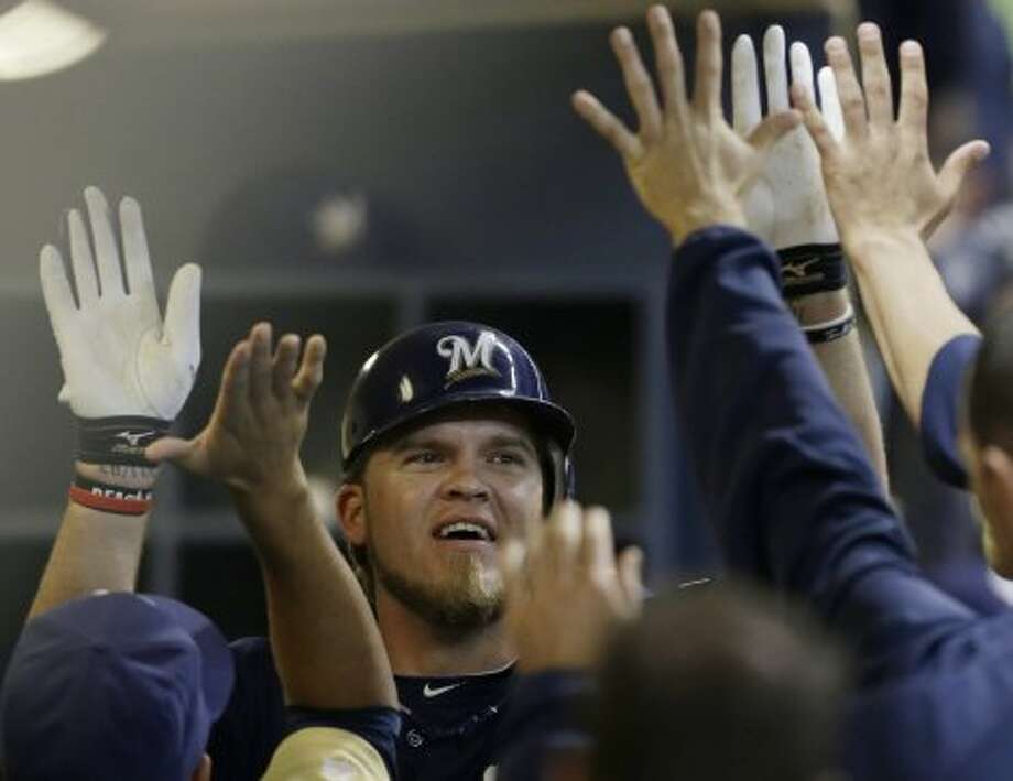 Corey Hart gets high-fives in the dugout after his home run. (JEFFREY PHELPS / Associated Press)