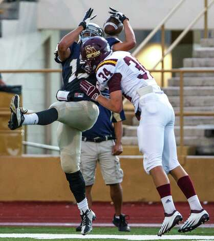Holy Cross's Greg Kelly (left) is unable to come down with the ball as San Antonio Christian's Potter Chase defends on the play during their game at Harlandale Memorial Stadium on Sept. 29, 2012.  MARVIN PFEIFFER/ mpfeiffer@express-news.net Photo: MARVIN PFEIFFER, Express-News / Express-News 2012