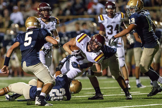 San Antonio Christian's Christian Clayton (center) is brought down by Holy Cross's Aaron Naranjo during their game at Harlandale Memorial Stadium on Sept. 29, 2012.  MARVIN PFEIFFER/ mpfeiffer@express-news.net Photo: MARVIN PFEIFFER, Express-News / Express-News 2012