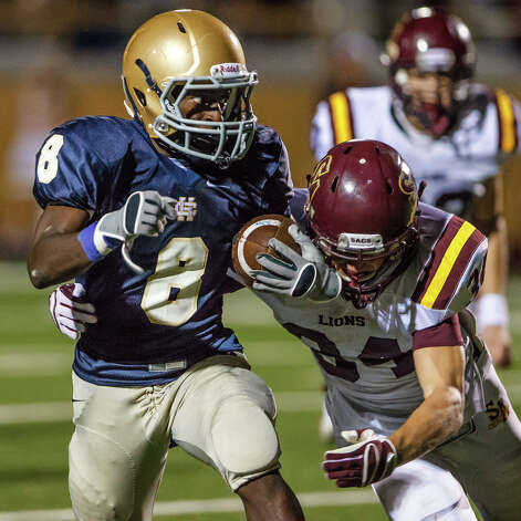 Holy Cross running back Kyron Davis (left) looks to avoid a tackle by San Antonio Christian's Potter Chase during the second half of their game at Harlandale Memorial Stadium on Sept. 29, 2012.  Holy Cross won the game 25-23.  MARVIN PFEIFFER/ mpfeiffer@express-news.net Photo: MARVIN PFEIFFER, Express-News / Express-News 2012
