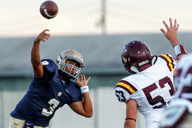 Holy Cross quarterback Sam Moreno gets a pass off over San Antonio Christian's Molak Christopher during the first quarter of their game at Harlandale Memorial Stadium on Sept. 29, 2012.  MARVIN PFEIFFER/ mpfeiffer@express-news.net Photo: MARVIN PFEIFFER, Express-News / Express-News 2012