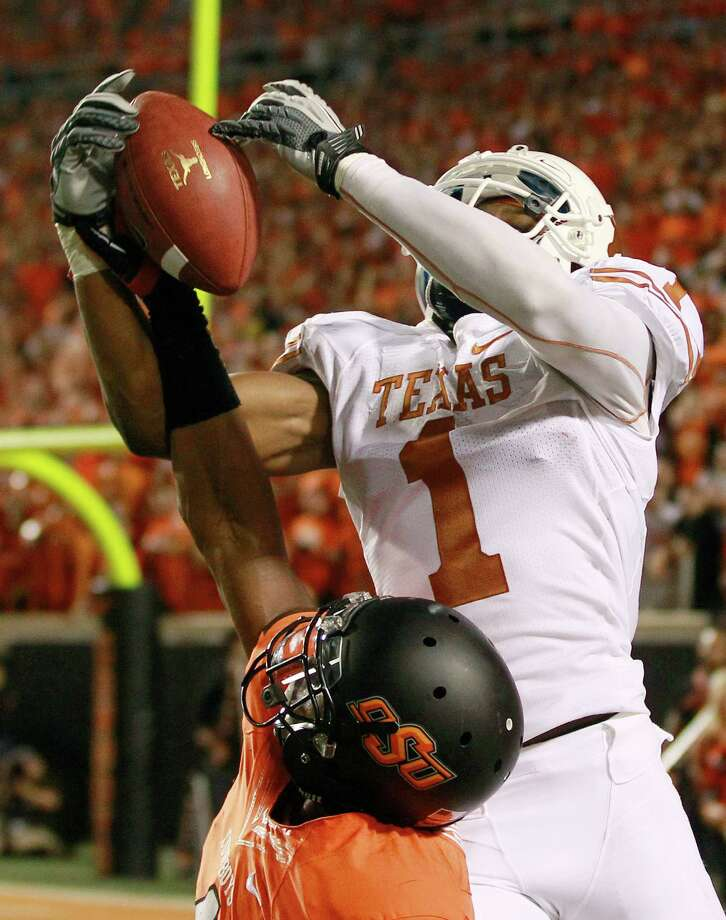 Texas wide receiver Mike Davis (1) catches a pass overOklahoma State cornerback Justin Gilbert (4) during the fourth quarter of an NCAA college football game in Stillwater, Okla., Saturday, Sept. 29, 2012. Texas won 41-36. (AP Photo/Sue Ogrocki) Photo: Sue Ogrocki, Associated Press / AP