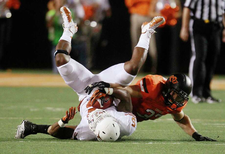 Oklahoma State linebacker Alex Elkins (37) tackles Texas running back Jeremy Hills (5) during the fourth quarter of an NCAA college football game in Stillwater, Okla., Saturday, Sept. 29, 2012. Texas won 41-36. (AP Photo/Sue Ogrocki) Photo: Sue Ogrocki, Associated Press / AP