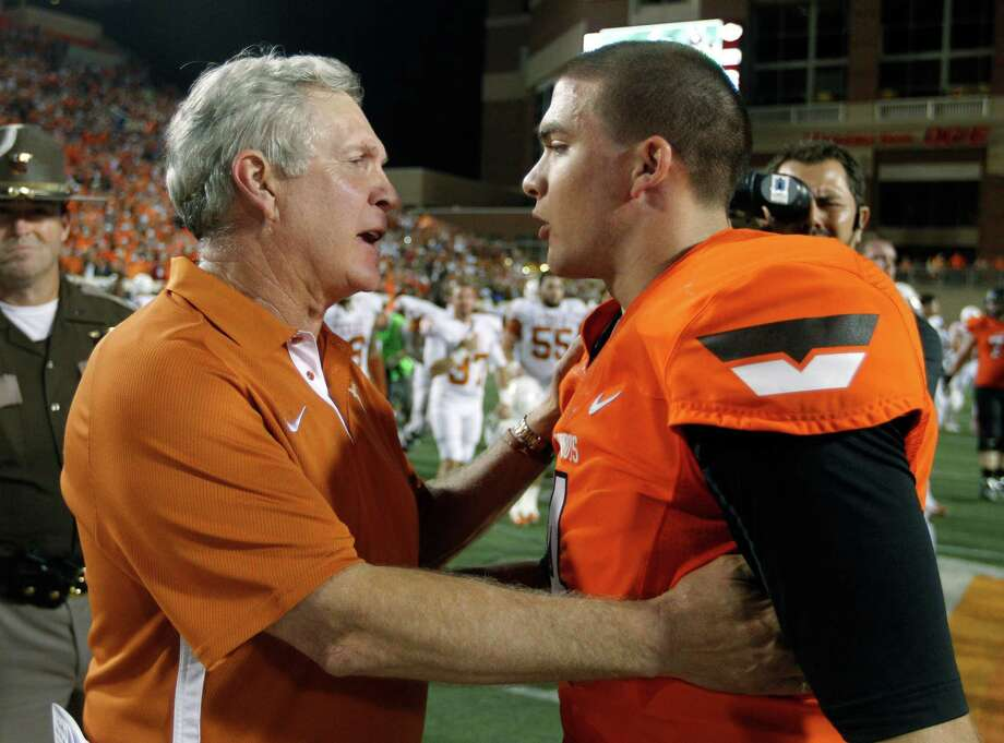 Texas coach Mack Brown, left, talks with Oklahoma State quarterback J.W. Walsh following an NCAA college football game in Stillwater, Okla., Saturday, Sept. 29, 2012. Texas won 41-36. (AP Photo/Sue Ogrocki) Photo: Sue Ogrocki, Associated Press / AP