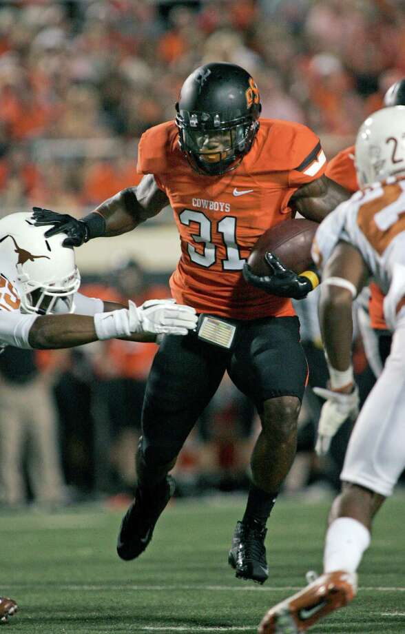 STILLWATER, OK - SEPTEMBER 29: Running back Jeremy Smith #31 of the Oklahoma State Cowboys breaks a tackle against the Texas Longhorns on September 29, 2012 at Boone Pickens Stadium in Stillwater, Oklahoma. Photo: Brett Deering, Getty Images / 2012 Getty Images