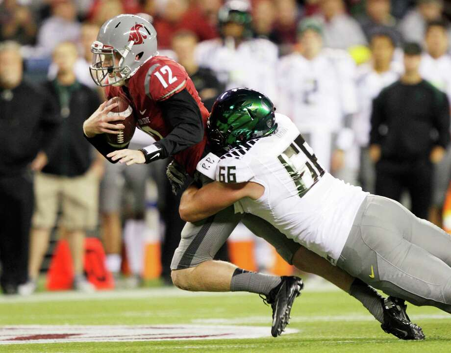 Oregon's Taylor Hart tackles Washington State quarterback Connor Halliday during the first half of an NCAA college football game, Saturday, Sept. 29, 2012, in Seattle. Photo: AP