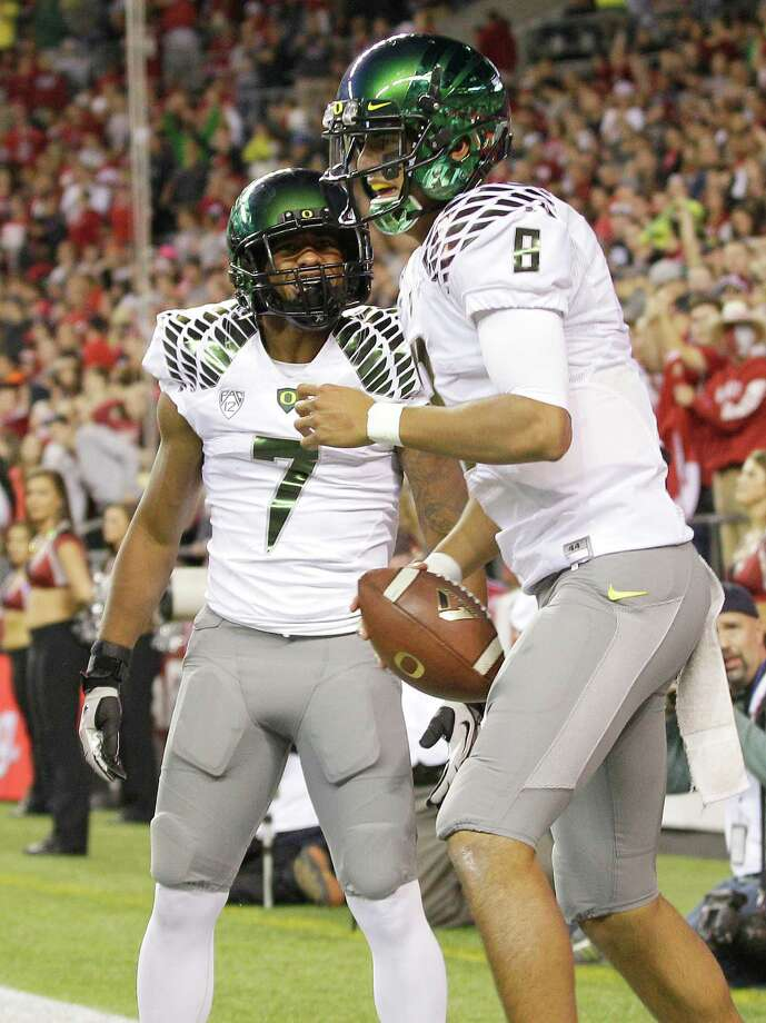 Oregon quarterback Marcus Mariota, right, celebrates his touchdown against Washington State with Keanon Lowe (7) during the first half of an NCAA college football game, Saturday, Sept. 29, 2012, in Seattle. Photo: AP