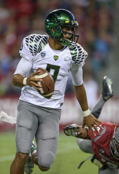SEATTLE, WA - SEPTEMBER 29:  Quarterback Marcus Mariota #8 of the Oregon Ducks rushes against the Wa