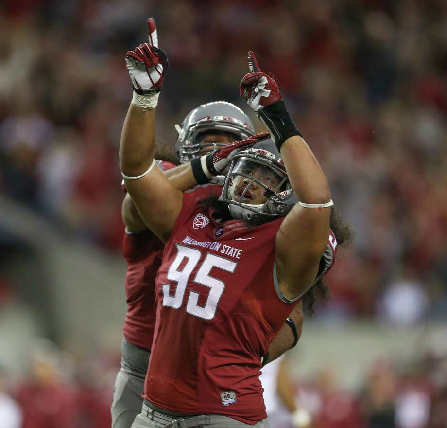 SEATTLE, WA - SEPTEMBER 29:  Ioane Gauta #95 of the Washington State Cougars celebrates with Kalafitoni Pole #98 after making a tackle against the Oregon Ducks on September 29, 2012 at CenturyLink Field in Seattle, Washington. Photo: Otto Greule Jr, Getty Images / 2012 Getty Images
