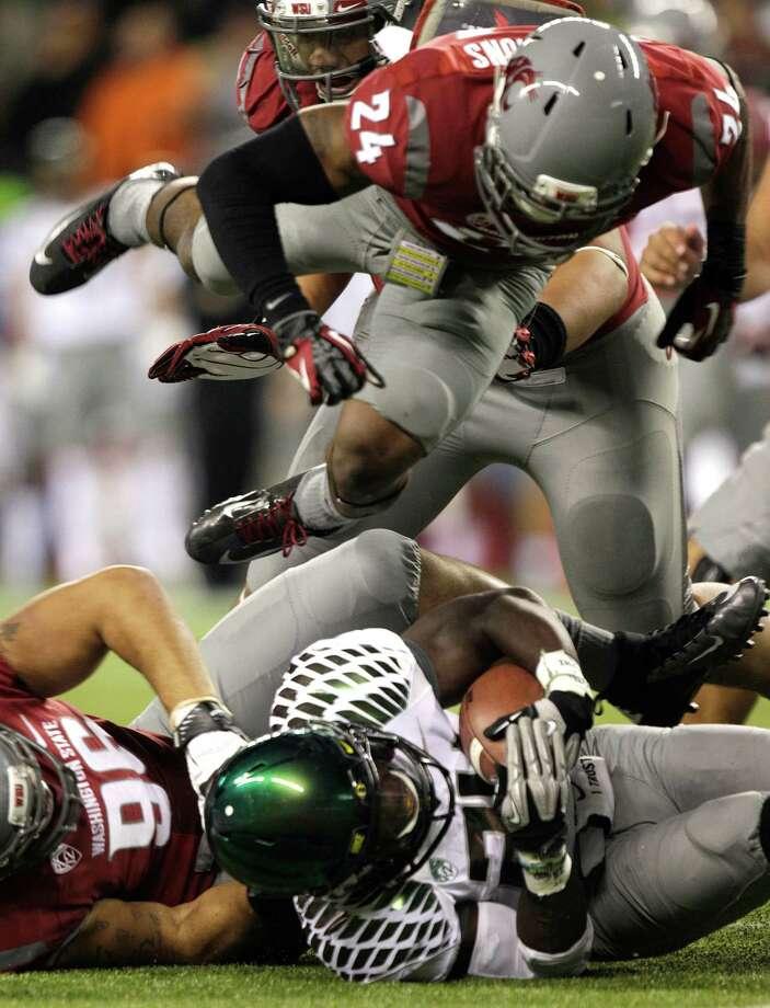 Washington State's Daniel Simmons, top, sails over Oregon's Kenjon Barner after Barner carried the ball in the first half of an NCAA college football game, Saturday, Sept. 29, 2012, in Seattle. Photo: AP