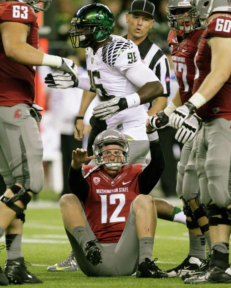 Washington State quarterback Connor Halliday is helped up after being sacked during the first half of an NCAA college football game against Oregon, Saturday, Sept. 29, 2012, in Seattle. Photo: AP