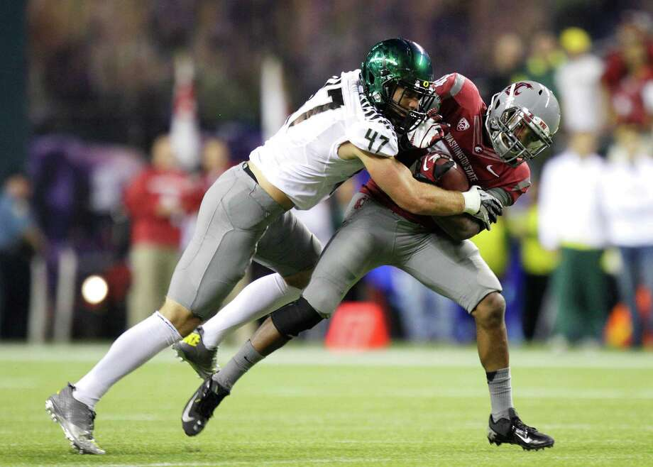 Oregon's Kiko Alonso, left, tackles Washington State's Teondray Caldwell during the first half of an NCAA college football game, Saturday, Sept. 29, 2012, in Seattle. Photo: AP