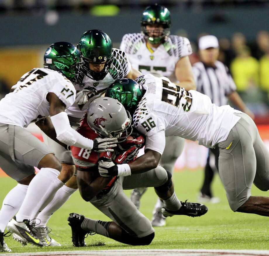 From left, Oregon's Terrance Mitchell, Kiko Alonso, and Dion Jordan tackle Washington State's Kristoff Williams during the first half of an NCAA college football game, Saturday, Sept. 29, 2012, in Seattle. Photo: AP