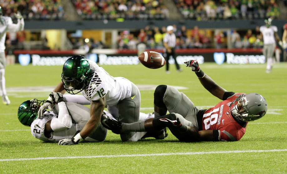 Washington State's Kristoff Williams (18) reaches for the ball but can't get it after Oregon's Terrance Mitchell (27), and Brian Jackson (12) broke up a pass play in the first half of an NCAA college football game, Saturday, Sept. 29, 2012, in Seattle. Photo: AP