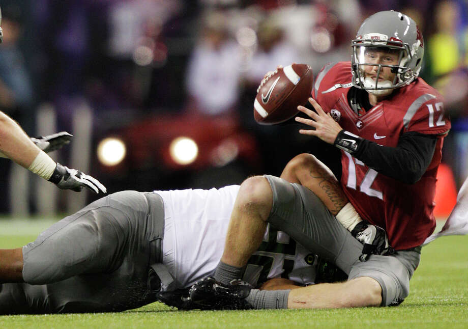 Washington State quarterback Connor Halliday, right, is sacked by Oregon's Wade Keliikipi in the first half of an NCAA college football game, Saturday, Sept. 29, 2012, in Seattle. Photo: AP