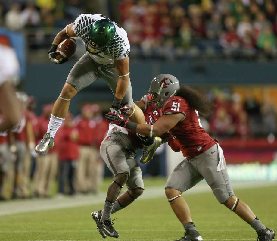 SEATTLE, WA - SEPTEMBER 29:  Tight end Colt Lyerla #15 of the Oregon Ducks leaps over linebacker Justin Sagote #51 and cornerback Damante Horton #6 of the Washington State Cougars on September 29, 2012 at CenturyLink Field in Seattle, Washington. Photo: Otto Greule Jr, Getty Images / 2012 Getty Images