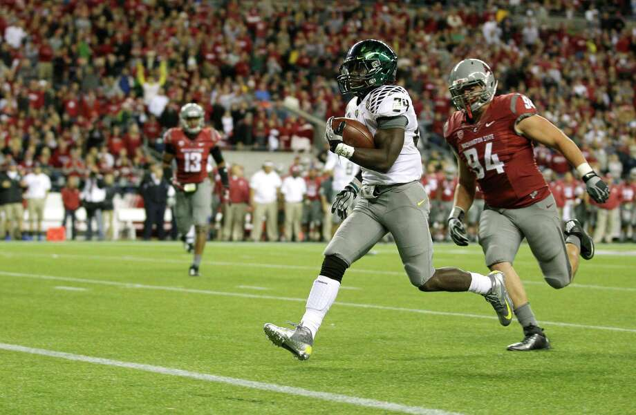 Oregon's Kenjon Barner, second from right, runs for a touchdown in the second half, ahead of Washington State's Robert Barber (94), in an NCAA college football game, Saturday, Sept. 29, 2012, in Seattle. Photo: AP