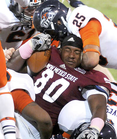 UTSA 35 - New Mexico State 14: New Mexico State tight end Perris Scoggins gets his helmet ripped off during an NCAA college football game against Texas-San Antonio on Saturday, Sept. 29, 2012, in Las Cruces, N.M.  Photo: Robin Zielinski, Associated Press / Las Cruces Sun-News
