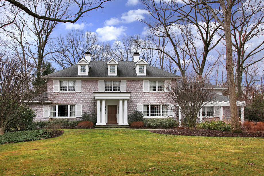 This white-washed red brick house on Bayberry Lane looks like a traditional colonial on the outside but its interior has a modern flair with many artistic features. Photo: Contributed Photo