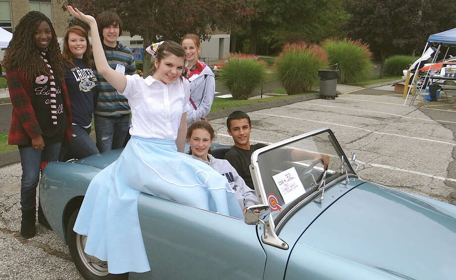 "Cast members of Notre Dame High School's production of ""Guys and Dolls"" with Steve Lunt's 1960 Austin Healey ""Bugeye"" Sprite at Saturday's car show. Photo: Mike Lauterborn / Fairfield Citizen contributed"