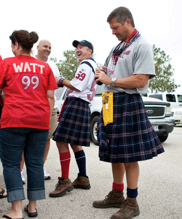 John Seele, of Deer Park, center, jokes with friends as he tailgates in his kilt with Corby Smith, of Deer Park, and friends before the Houston Texans and Tennessee Titans game outside Reliant Stadium on Sunday, Sept. 30, 2012, in Houston. Photo: Nick De La Torre, Houston Chronicle / © 2012  Houston Chronicle