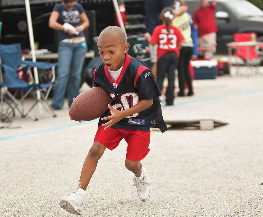 Justin Butler, of Houston, makes moves as he runs back a pass as he plays with friends before the Houston Texans game against the Tennessee Titans outside Reliant Stadium on Sunday, Sept. 30, 2012, in Houston. Photo: Nick De La Torre, Houston Chronicle / © 2012  Houston Chronicle