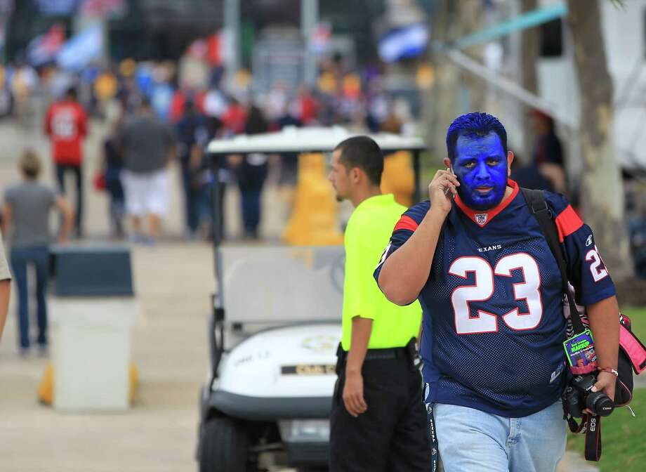 Israel Lozoya, of the McAllen area, walks through the Blue lot with a blue face at Reliant Stadium on Sunday, Sept. 30, 2012, in Houston. Photo: Karen Warren, Houston Chronicle / © 2012  Houston Chronicle