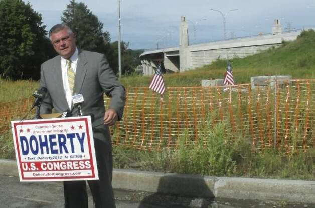 Republican 1st Congressional District  candidate Brendan Doherty speaks to the media in Tiverton, R.I., Thursday,  Sept. 6, 2012. Doherty said he wants the federal government to intervene to stop the state from imposing tolls on the new Sakonnet River Bridge, right rear. (Michelle R. Smith / Associated Press)