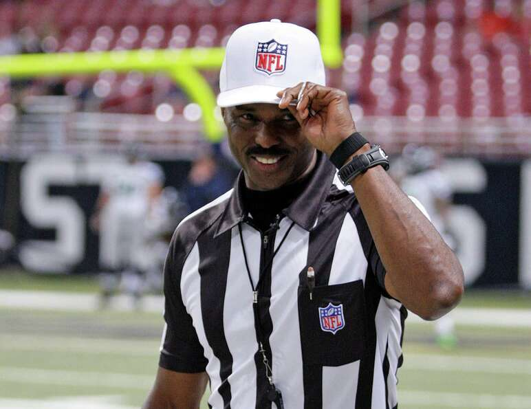 Referee Mike Carey tips his cap to the fans as he walks onto the field before an NFL football game