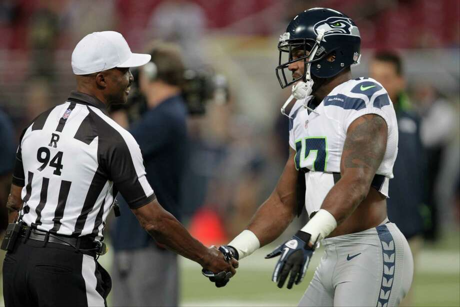 Referee Mike Carey (94) is greeted by Seattle Seahawks wide receiver Braylon Edwards  before an NFL football game against the St. Louis Rams Sunday, Sept. 30, 2012, in St. Louis. Photo: AP