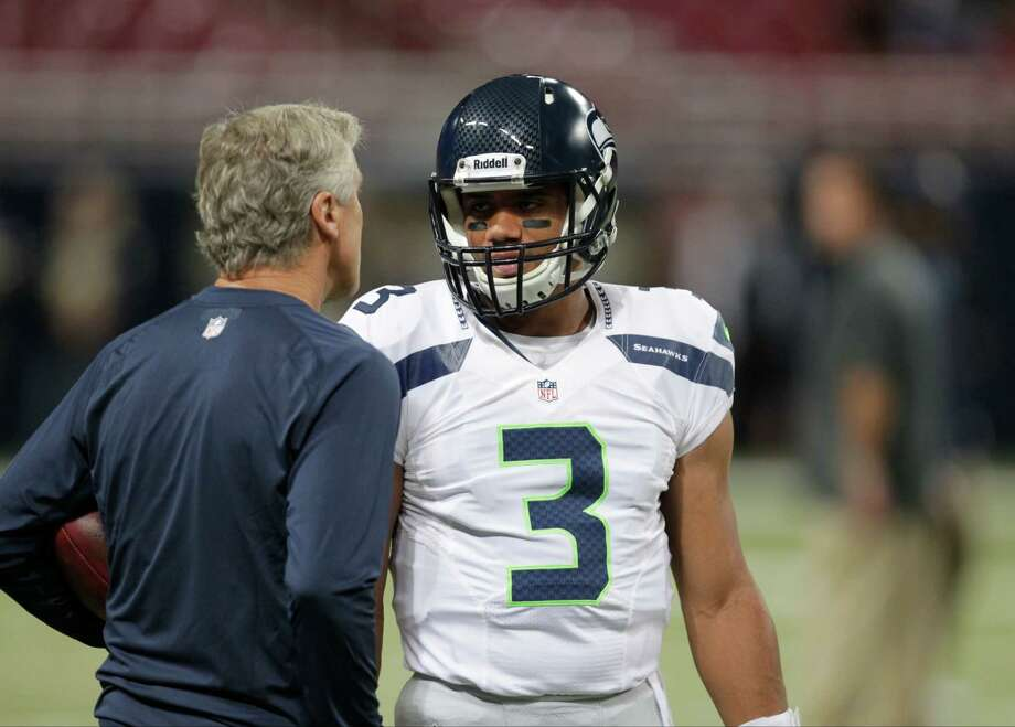 Seattle Seahawks quarterback Russell Wilson talks with head coach Pete Carroll before an NFL football game against the St. Louis Rams Sunday, Sept. 30, 2012, in St. Louis. Photo: AP