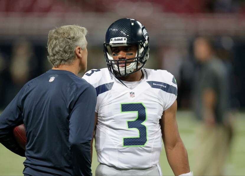 Seattle Seahawks quarterback Russell Wilson talks with head coach Pete Carroll before an NFL footbal