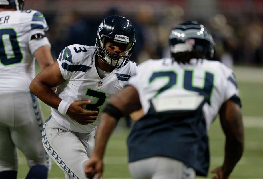 Seattle Seahawks quarterback Russell Wilson (3) hands the football to running back Marshawn Lynch before an NFL football game  against the St. Louis Rams Sunday, Sept. 30, 2012, in St. Louis. Photo: AP