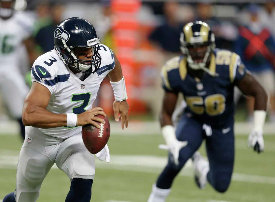 Seattle Seahawks quarterback Russell Wilson runs from St. Louis Rams outside linebacker Jo-Lonn Dunbar during the first half of an NFL football game Sunday, Sept. 30, 2012, in St. Louis. Photo: AP