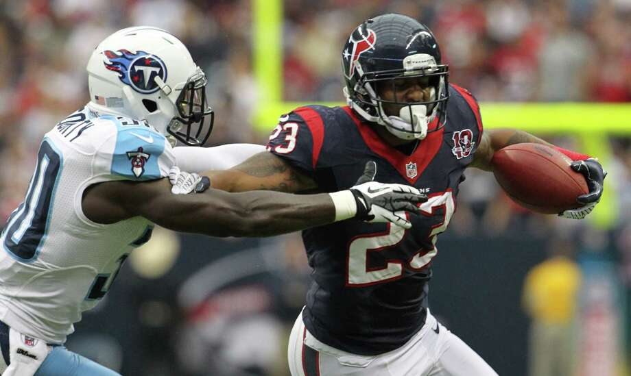 Houston Texans running back Arian Foster (23) pushes away from Tennessee Titans cornerback Jason McCourty (30) during the first quarter at Reliant Stadium on Sunday, Sept. 30, 2012, in Houston. Photo: Nick De La Torre, Houston Chronicle / © 2012  Houston Chronicle