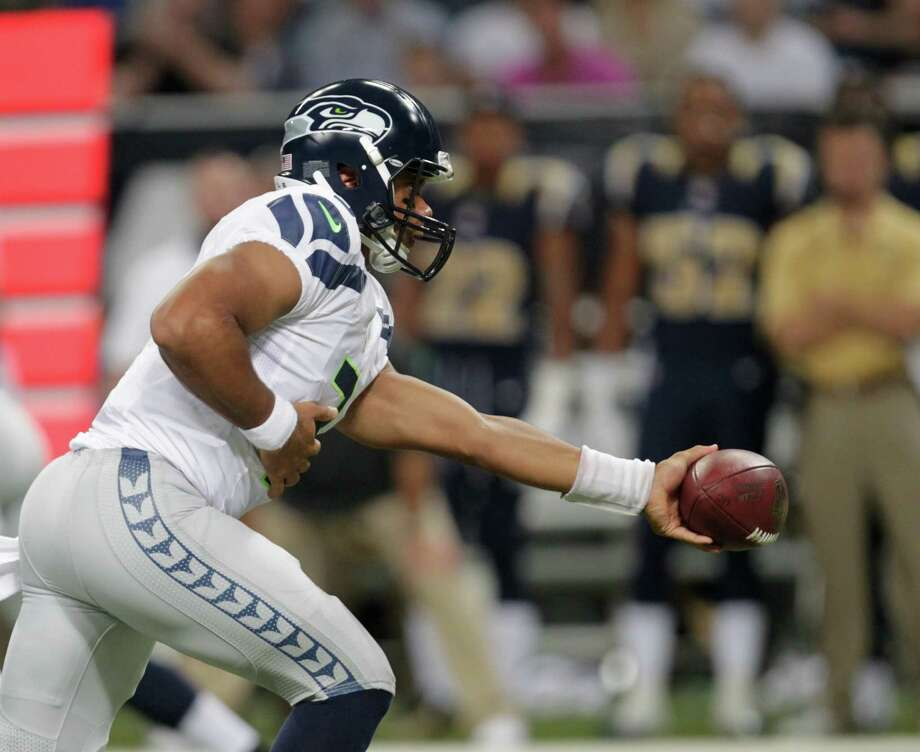 Seattle Seahawks quarterback Russell Wilson (3) hands the football off during the first half of an NFL football game against the St. Louis Rams Sunday, Sept. 30, 2012, in St. Louis. Photo: AP