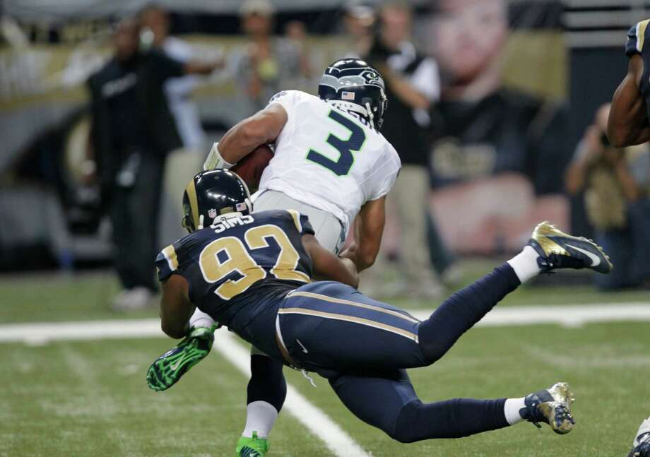 Seattle Seahawks quarterback Russell Wilson (3) is sacked by St. Louis Rams defensive end Eugene Sims (92)