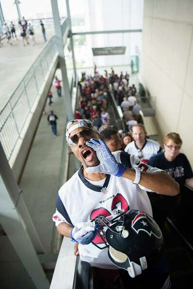 Houston Texans fan Benny Sanders cheers as he takes the escalator to the upper deck to watch his tea