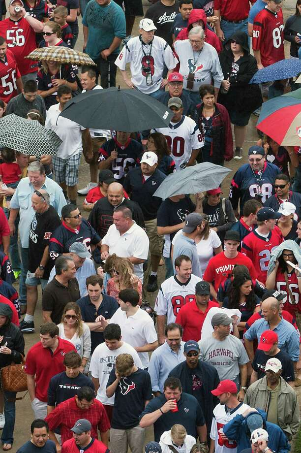 Fans wait in a light rain to enter the stadium to watch the Houston Texans face the Tennessee Titans at Reliant Stadium on Sunday, Sept. 30, 2012, in Houston. Photo: Smiley N. Pool, Houston Chronicle / © 2012  Houston Chronicle