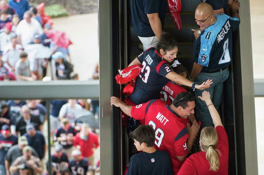 Houston Texans fans exchange high fives as the ride escalators into the stadium to watch their team face the Tennessee Titans at Reliant Stadium on Sunday, Sept. 30, 2012, in Houston. Photo: Smiley N. Pool, Houston Chronicle / © 2012  Houston Chronicle