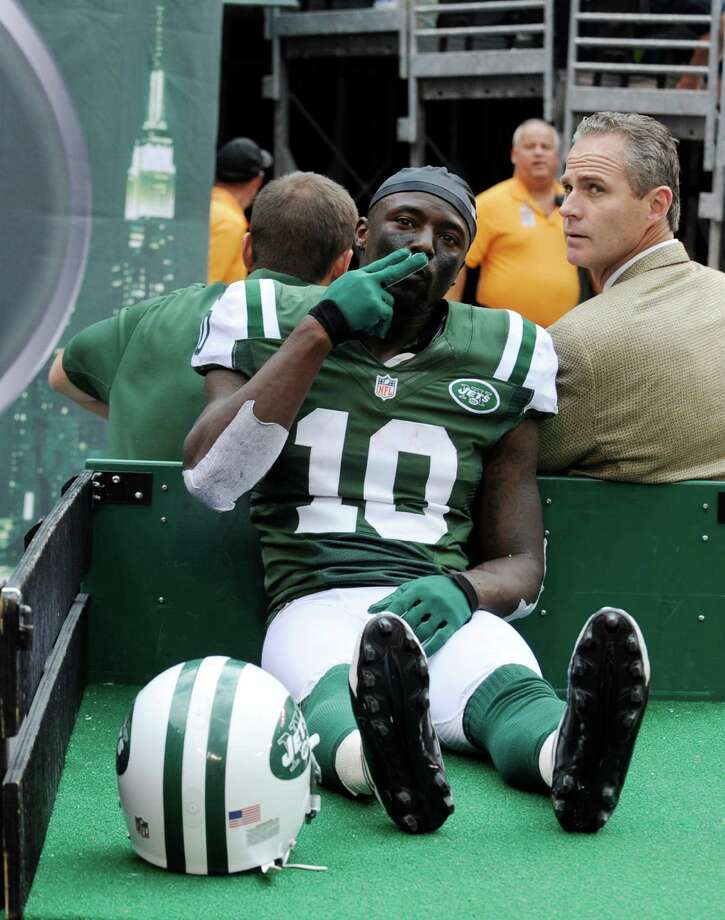 New York Jets wide receiver Santonio Holmes (10) gestures to fans as he is carted off the field after being injured during the second half of an NFL football game against the San Francisco 49ers Sunday, Sept. 30, 2012, in East Rutherford, N.J. (AP Photo/Bill Kostroun) Photo: Bill Kostroun / FR59151 AP