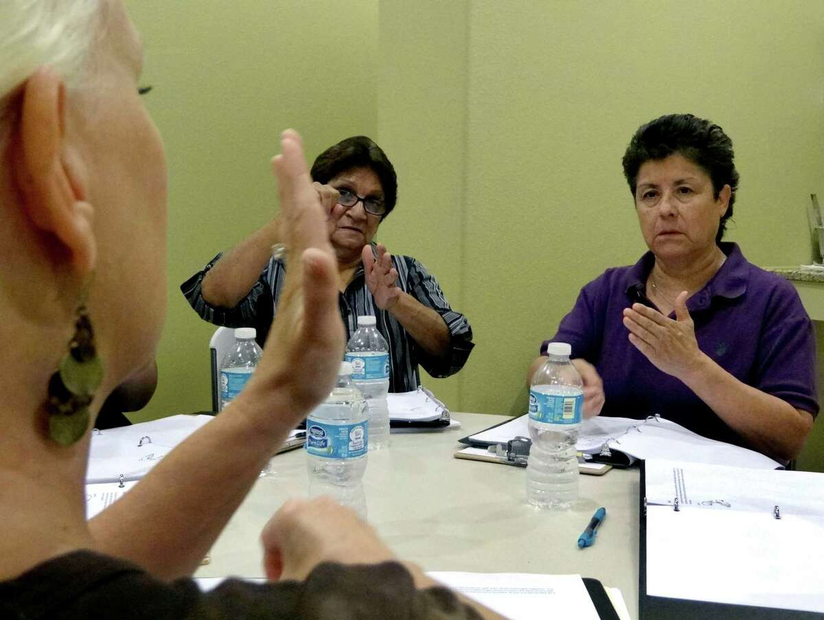 Della Lopez, right, a Navy veteran, and Maria Reyes, in-take coordinator at Project MEND, receive training in American Sign Language from Kay Chiodo, left, on Tuesday, Sept. 25, 2012. Sales of the Veterans Cash lottery ticket, which helps fund Project MEND, are down.