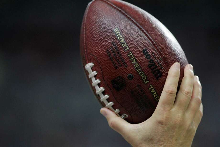 An official holds a football
