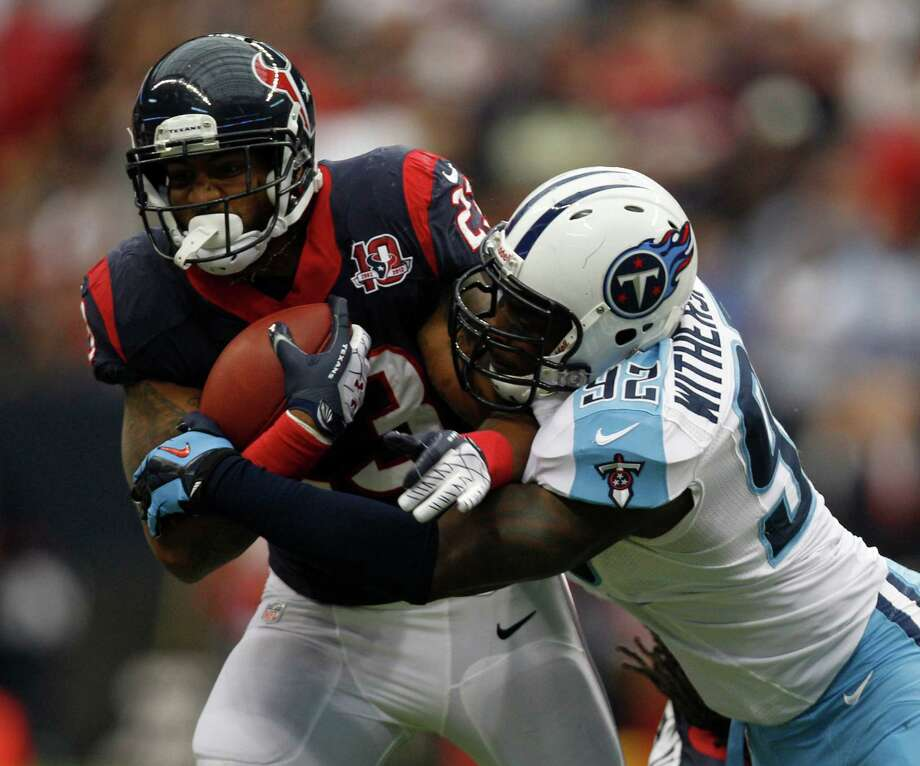 Houston Texans running back Arian Foster (23) is tackled by Tennessee Titans middle linebacker Will Witherspoon (92) during the first quarter at Reliant Stadium on Sunday, Sept. 30, 2012, in Houston. Photo: Brett Coomer, Houston Chronicle / © 2012  Houston Chronicle
