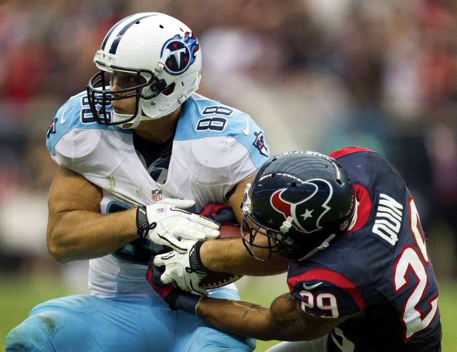 Houston Texans strong safety Glover Quin (29) reaches in to try and strip the ball from Tennessee Titans tight end Craig Stevens (88) after a reception during the fourth quarter at Reliant Stadium on Sunday, Sept. 30, 2012, in Houston. The Texans beat the Titans 38-14. Photo: Brett Coomer, Houston Chronicle / © 2012  Houston Chronicle