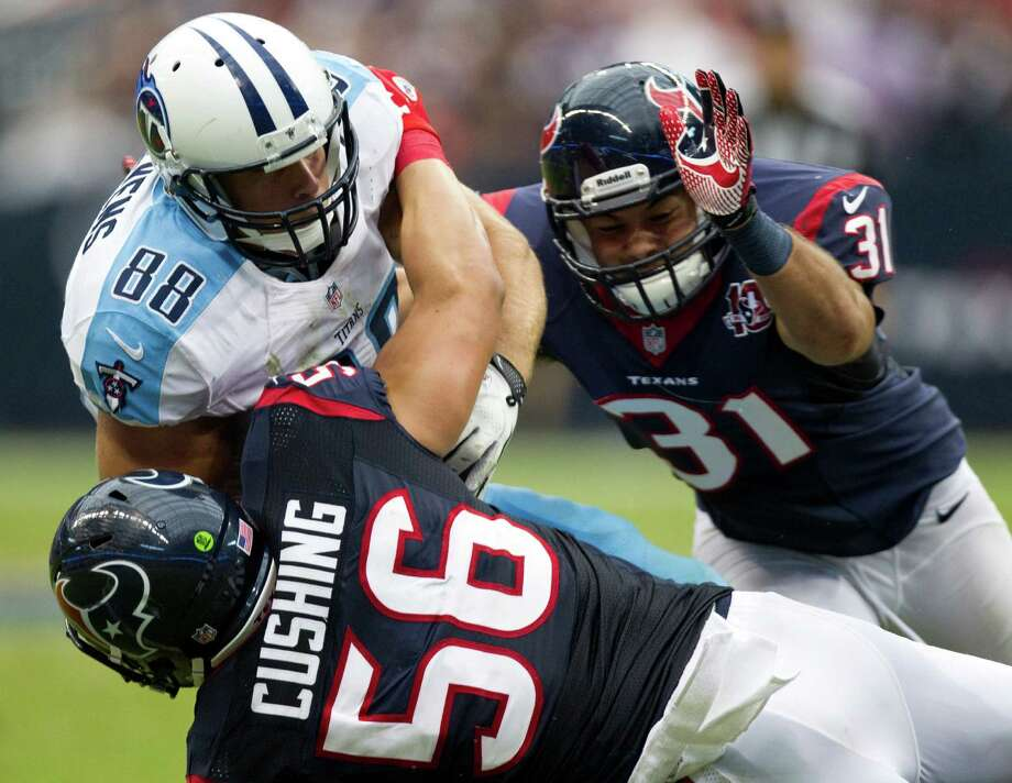 Houston Texans inside linebacker Brian Cushing (56) and safety Shiloh Keo (31) stop Tennessee Titans tight end Craig Stevens (88) after a reception during the fourth quarter at Reliant Stadium on Sunday, Sept. 30, 2012, in Houston. The Texans beat the Titans 38-14. Photo: Brett Coomer, Houston Chronicle / © 2012  Houston Chronicle