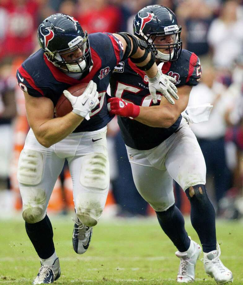 Houston Texans defensive end J.J. Watt (99) is pushed by linebacker Brian Cushing as he picks up a fumble by Tennessee Titans quarterback Matt Hasselbeck during the fourth quarter at Reliant Stadium on Sunday, Sept. 30, 2012, in Houston. The Texans beat the Titans 38-14. Photo: Brett Coomer, Houston Chronicle / © 2012  Houston Chronicle