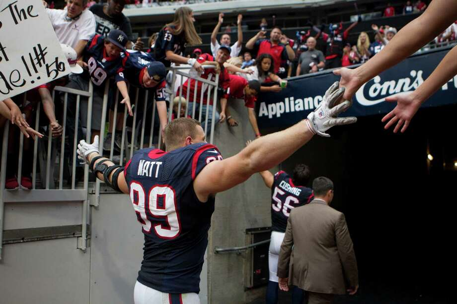 Houston Texans defensive end J.J. Watt (99) slaps hands with fans as he leaves the field after the Texans beat the Tennessee Titans at Reliant Stadium on Sunday, Sept. 30, 2012, in Houston. The Texans beat the Titans 38-14. Photo: Brett Coomer, Houston Chronicle / © 2012  Houston Chronicle